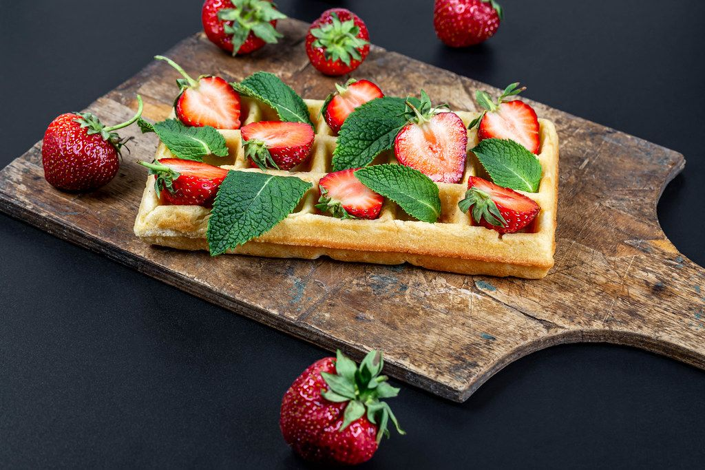 Belgian waffle with sliced strawberries and mint leaves on an old kitchen board