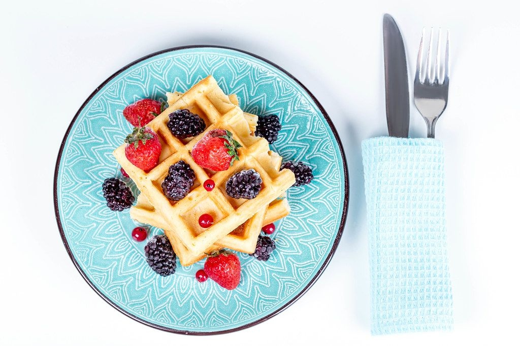 Belgian waffles with berries in a plate on white, top view
