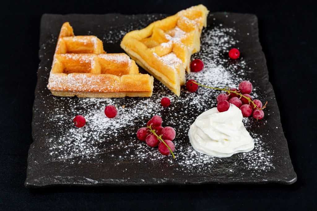 Belgian waffles with red currant, powdered sugar and whipped cream on a black background