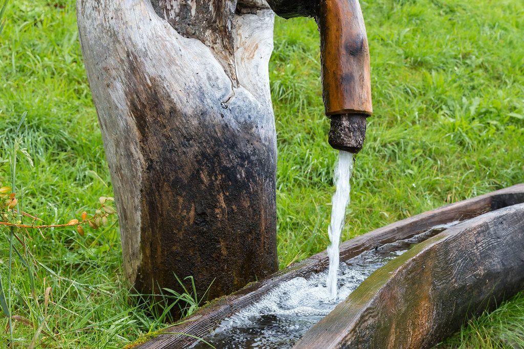 Berg-Quellwasser fließt aus einem Holzbrunnen in Alpbach in Tirol, Österreich
