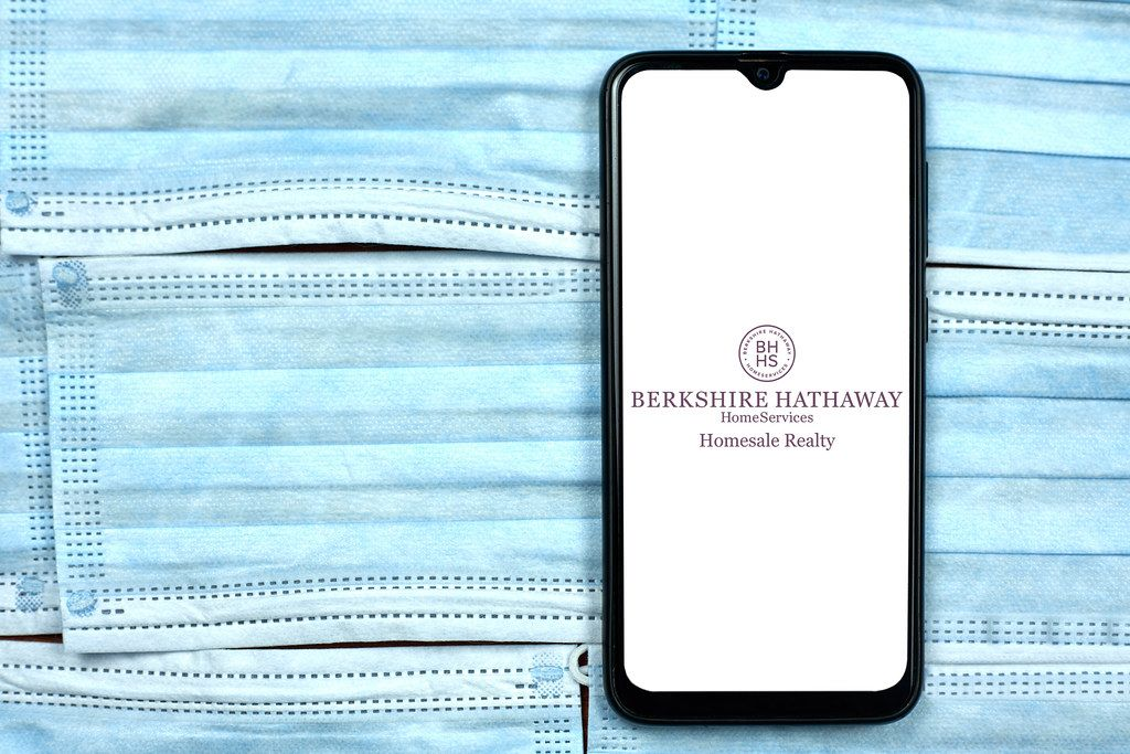 Berkshire Hathaway Home Services logo on smartphone display over the face masks
