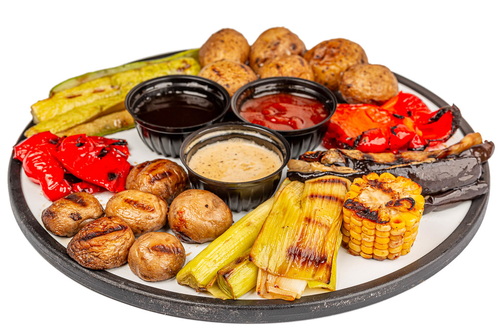 Big pieces of different grilled vegetables and champignons with sauces