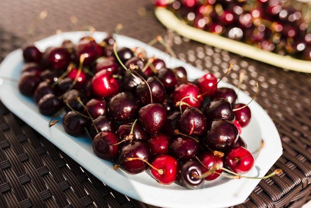 Big Red Cherries On The White Dish