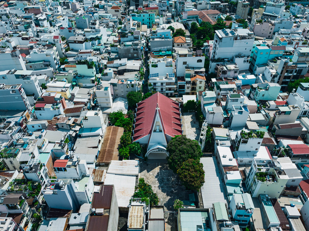 Bird View Drone Photo of a local Catholic Church within a Residential Area with many Houses and Alleys in Ho Chi Minh City, Vietnam