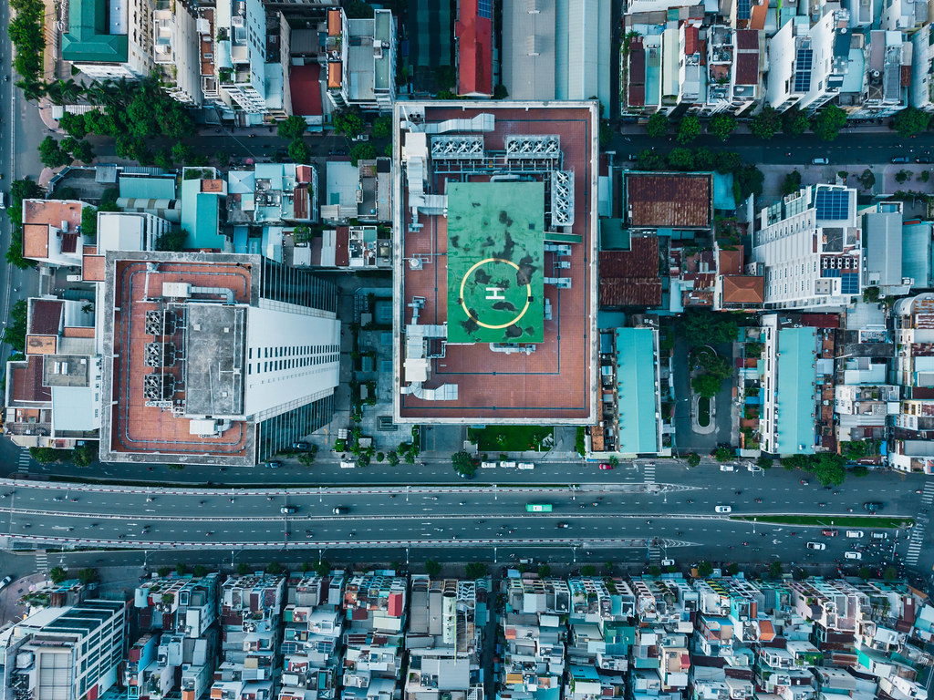 Bird View Drone Photo of Helicopter Landing on a Tall Building next to a busy Street in District 4 in Ho Chi Minh City, Vietnam