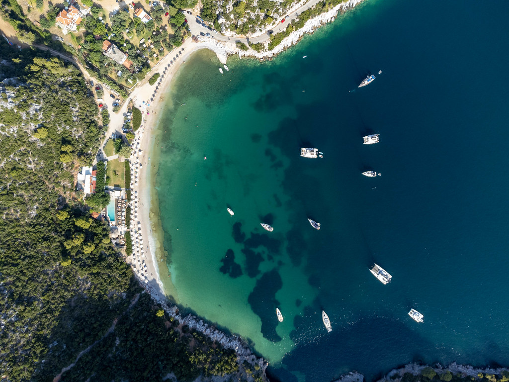 Bird's eye view: Limnonari bay with pine-covered hills, boats and beach on Skopelos