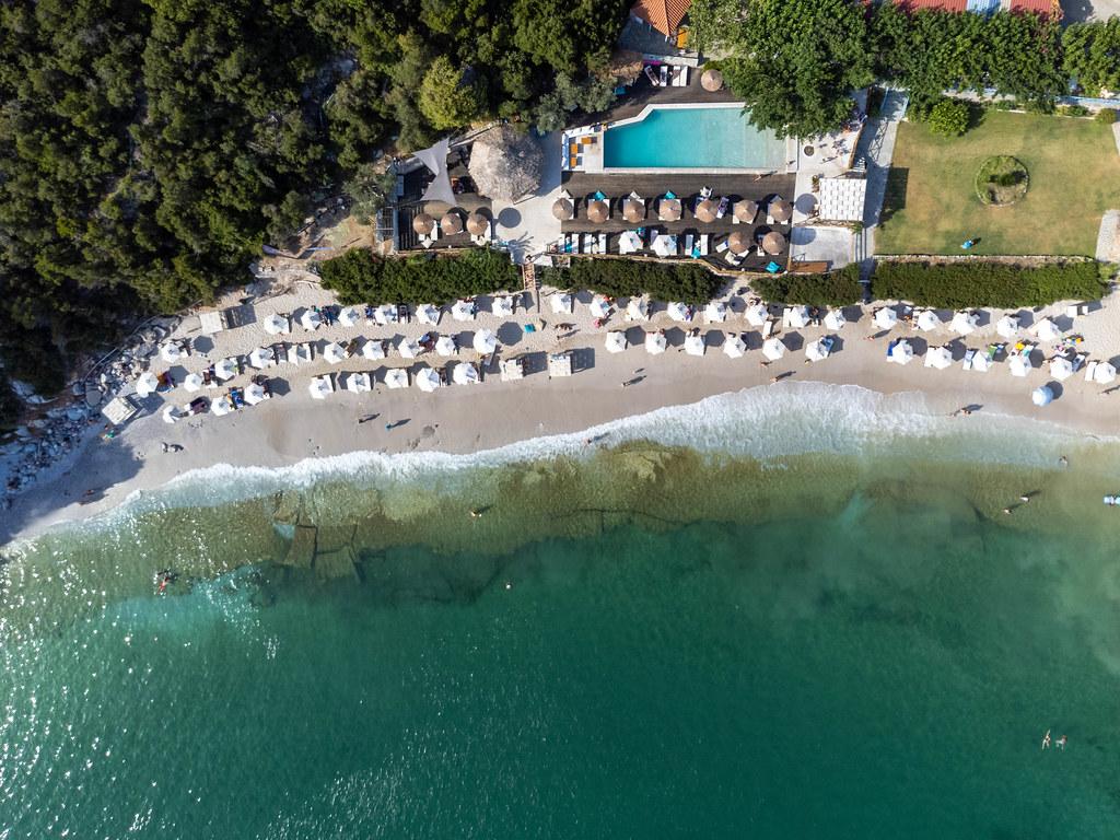 Bird's eye view of Limnonari beach with white hexagonal and straw parasols and swimming pool