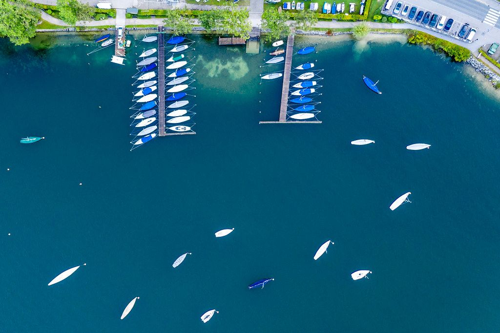 Bird's eye view: sailboats with covers resting in winter around two piers at Tegernsee lake in Bavaria