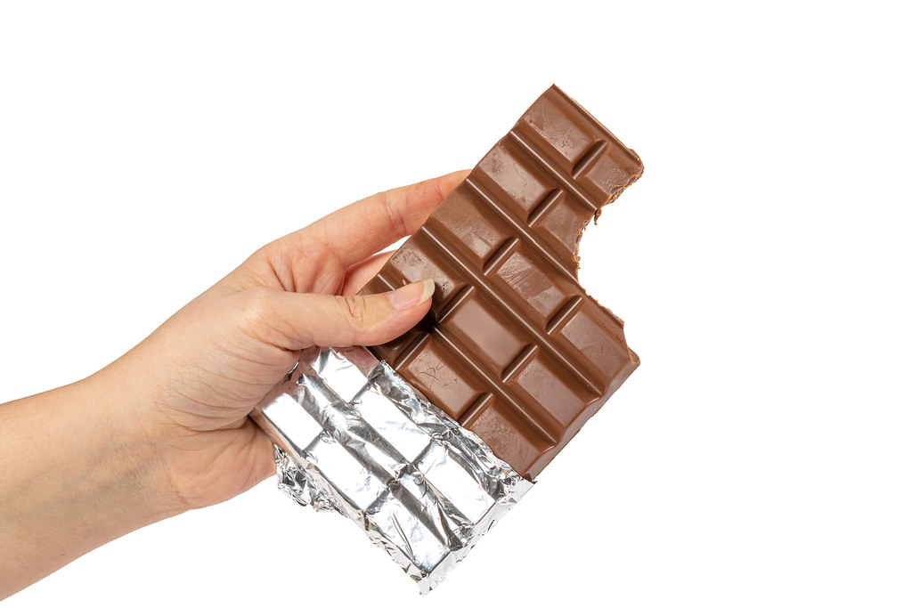 Bitten chocolate bar in a woman's hand