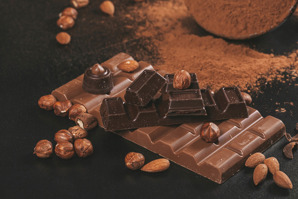 Bitter chocolate and milk chocolate with nuts, dark background
