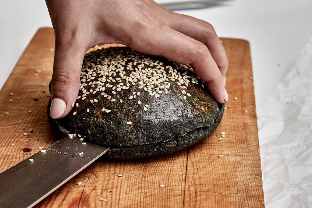 Black bread buns. Slicing black hamburger bread
