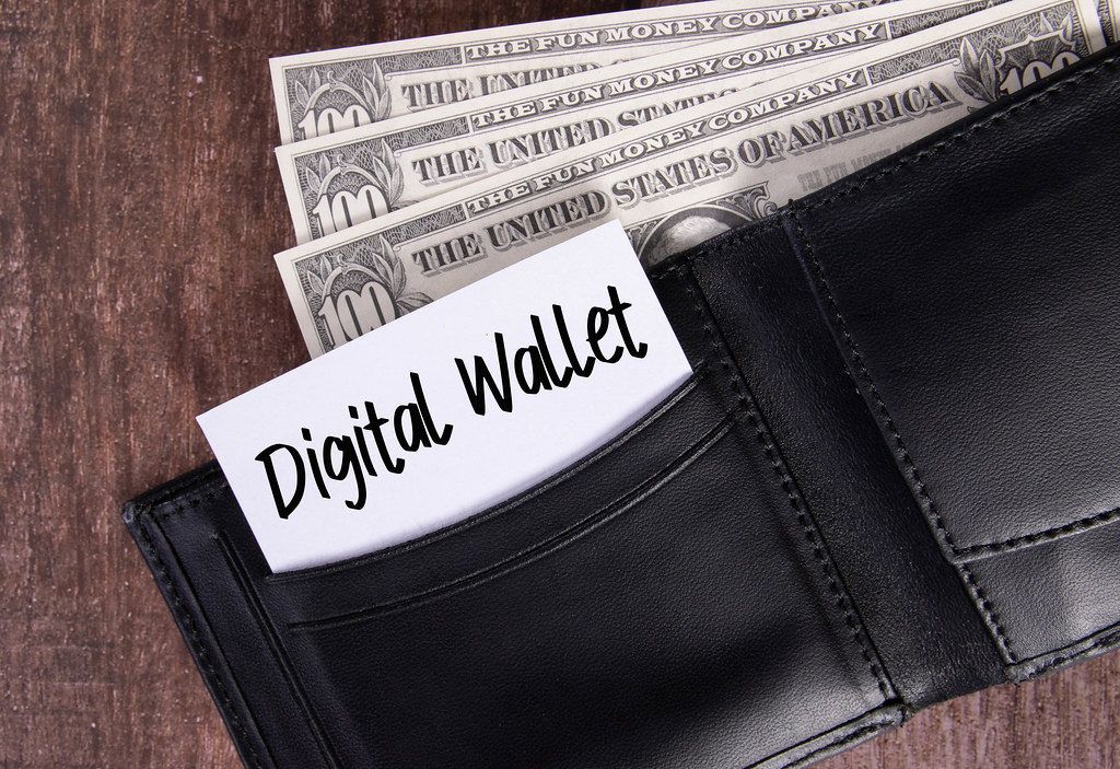 Black leather wallet with Dollar banknotes and note with Digital Wallet text