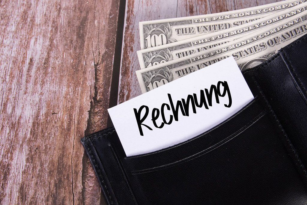 Black leather wallet with Dollar banknotes and note with Rechnung text