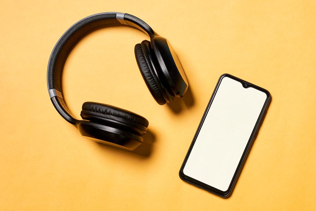 Black music headphones and smartphone on yellow background