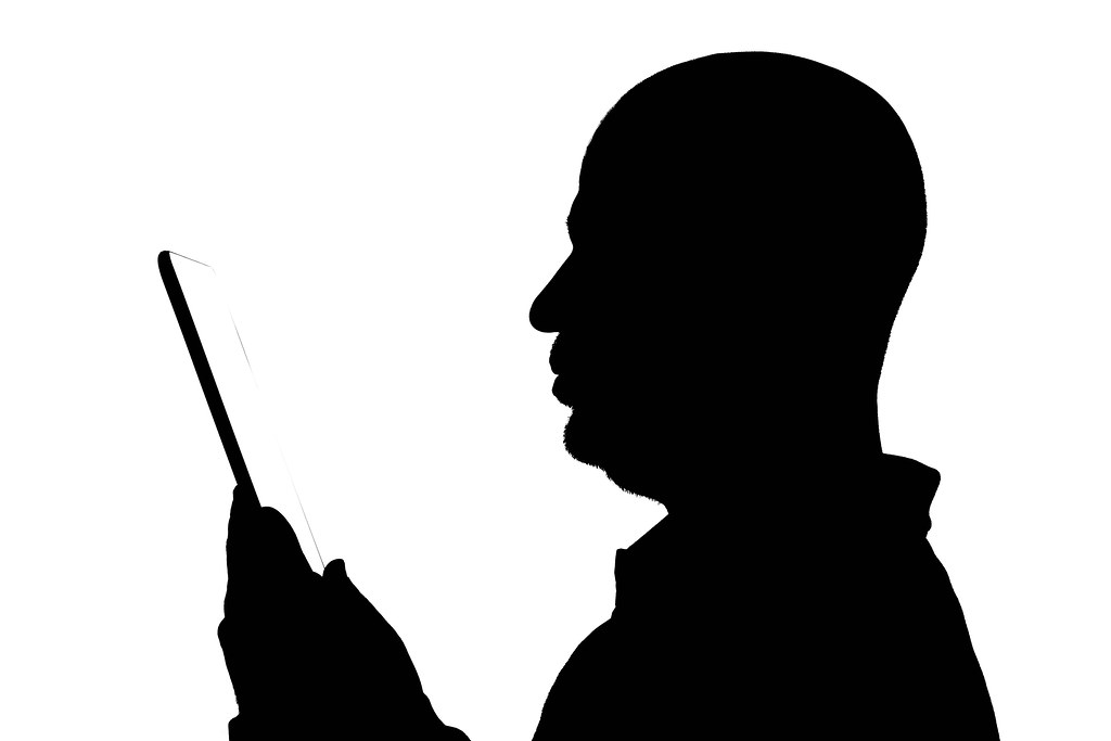 Black silhouette of a businessman with tablet against the white background