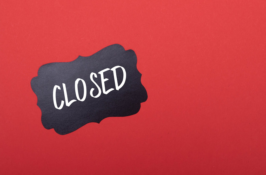 Black sticker with Closed text on red background