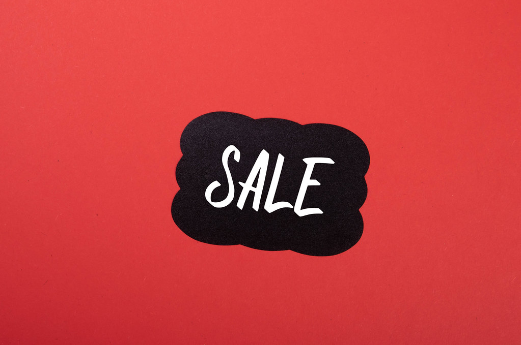 Black sticker with Sale text on red background