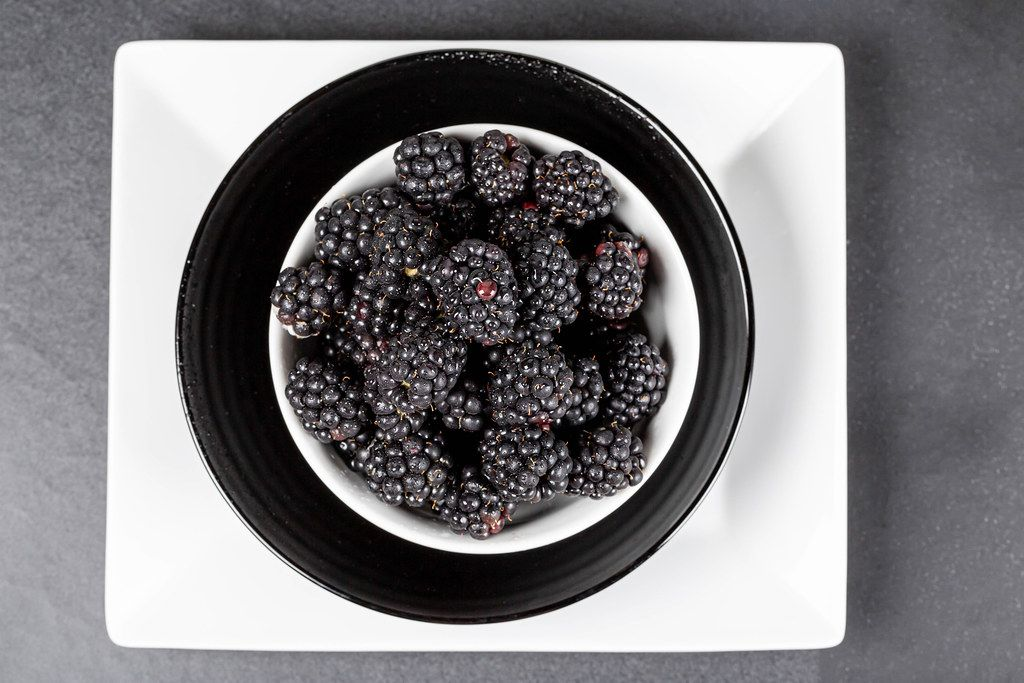 Blackberries in bowls on a dark background, top view
