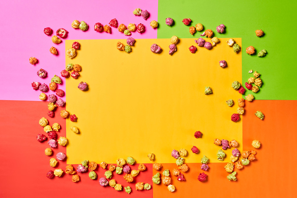 Blank yellow paper with popcorns on colorful background