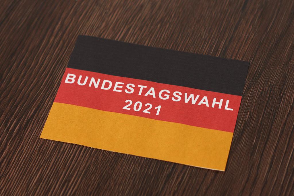 """Blatt in den Farben der deutschen Flagge mit Schrift """"Bundestagswahl 2021"""" auf hölzernem Hintergrund"""