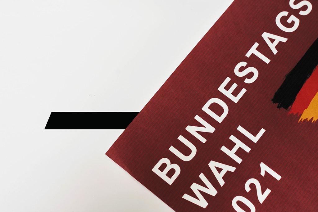 """Blatt mit der Schrift """"Bundestagswahl 2021"""" in Weiß auf Rot und der deutschen Flagge vor der Wahlurne"""