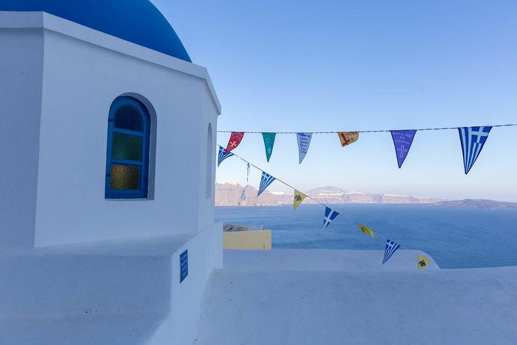 Blau und weiss auf Santorin: weißes Gebäude mit blauer Kuppel, Fahnen und dem Meer