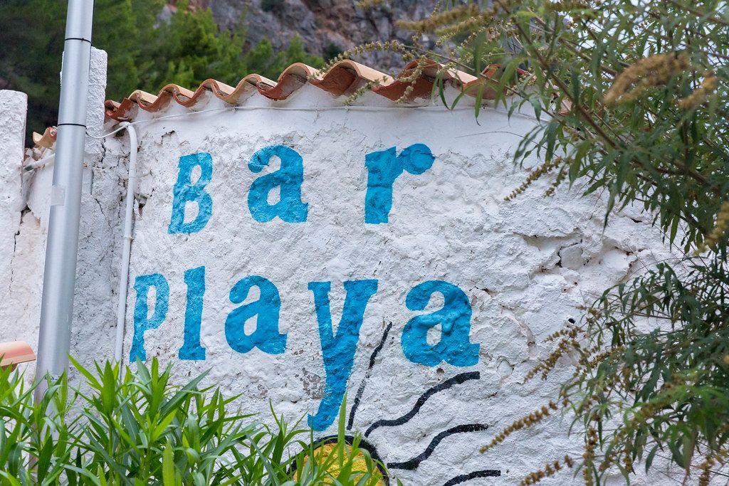 "Blaue Schrift ""Bar Playa"" (""Strandbar"") auf der weißen Wand in Port de Sa Calobra, Mallorca"
