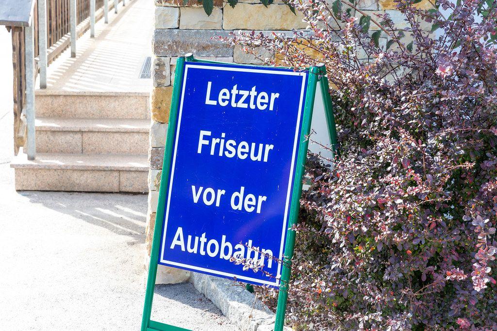"""Blaues Schild """"Letzter Friseur vor der Autobahn"""" in den Alpen in Österreich"""