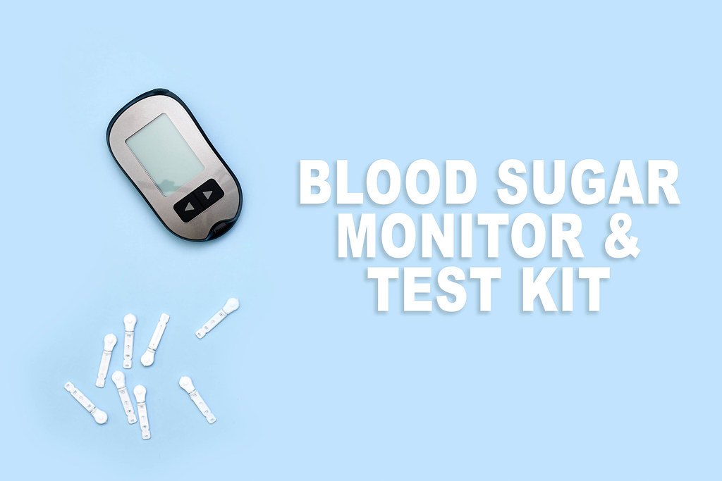 Blood sugar monitor and test kit on blue background
