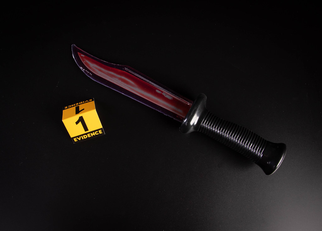 Bloody knife lies on a black background with evidence marker