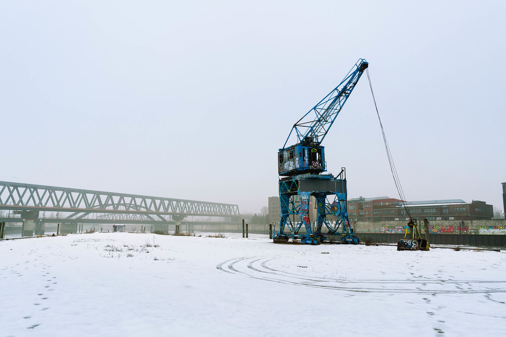 Blue abandoned crane covered with graffiti standing out in snow covered industrial district of Hamburg