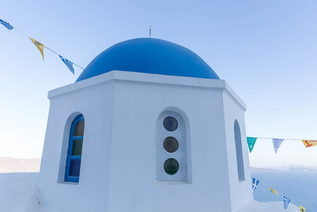 Blue and white in a typical Santorini picture of the famous church with a blue dome and triangular flags