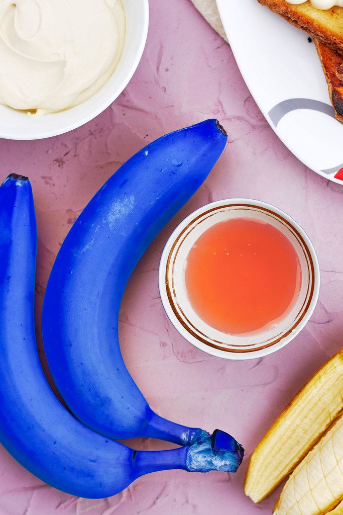 Blue bananas with a cup of tea. Symbol of poisonous food, pop art, difference