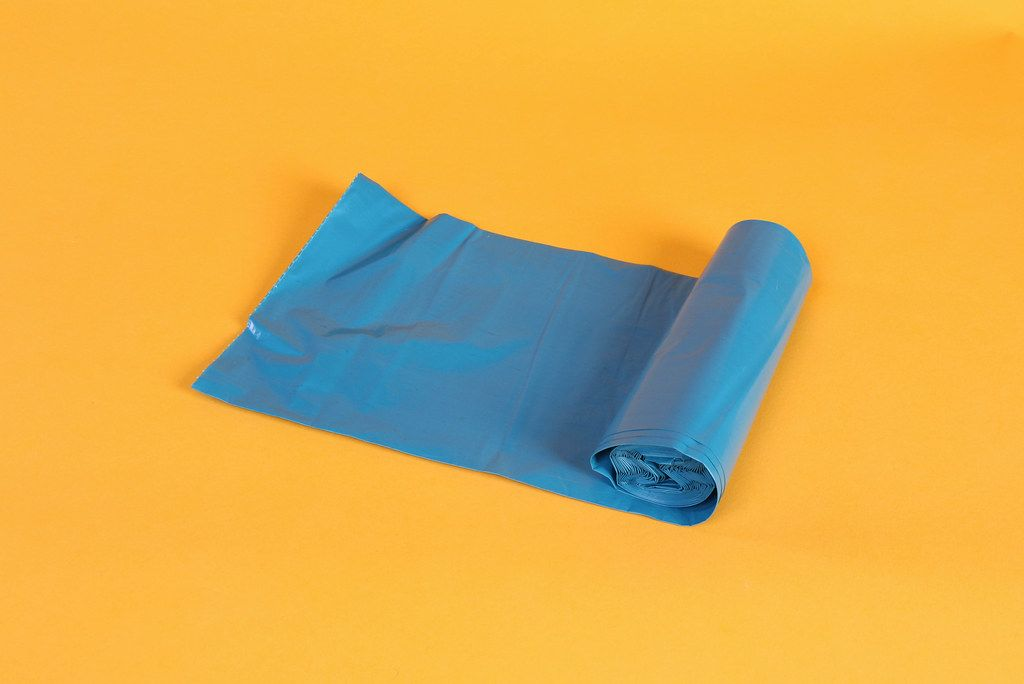 Blue bin bag roll on orange background