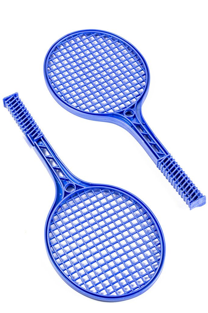 Blue plastic tennis rackets on white background