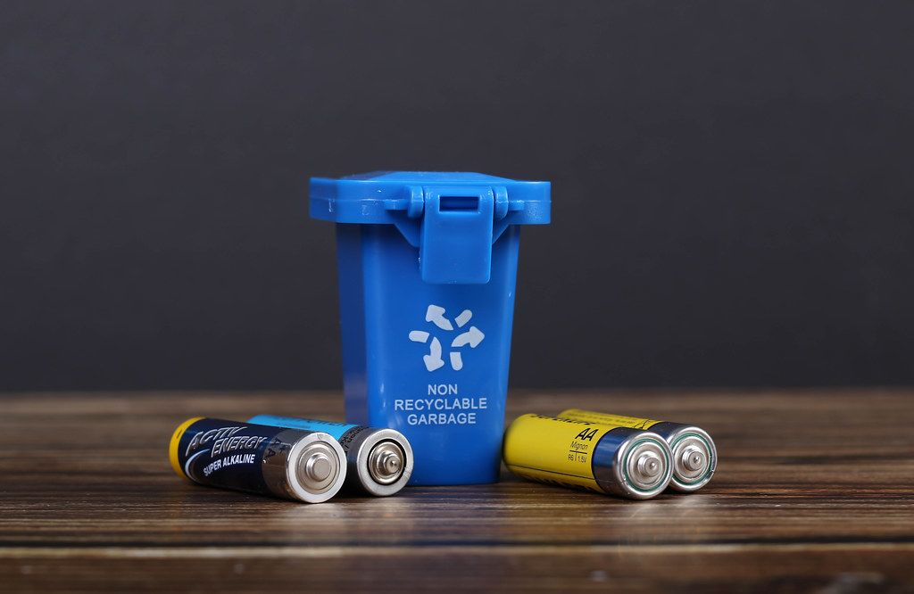 Blue recycle bin with batteries