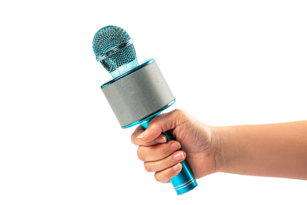 Blue toy microphone in women hand