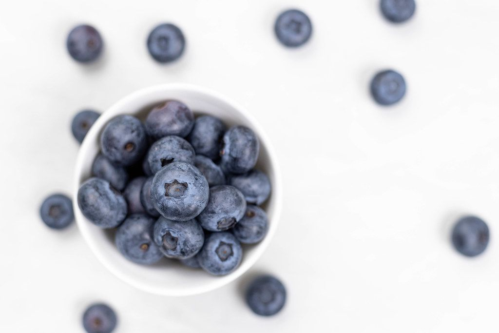 Blueberries in the bowl with blurred background and copy space