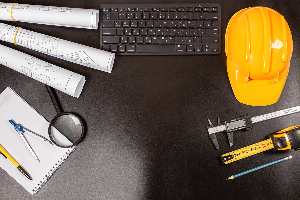 Blueprints, drawing tools, hard hat and keyboard on a dark background