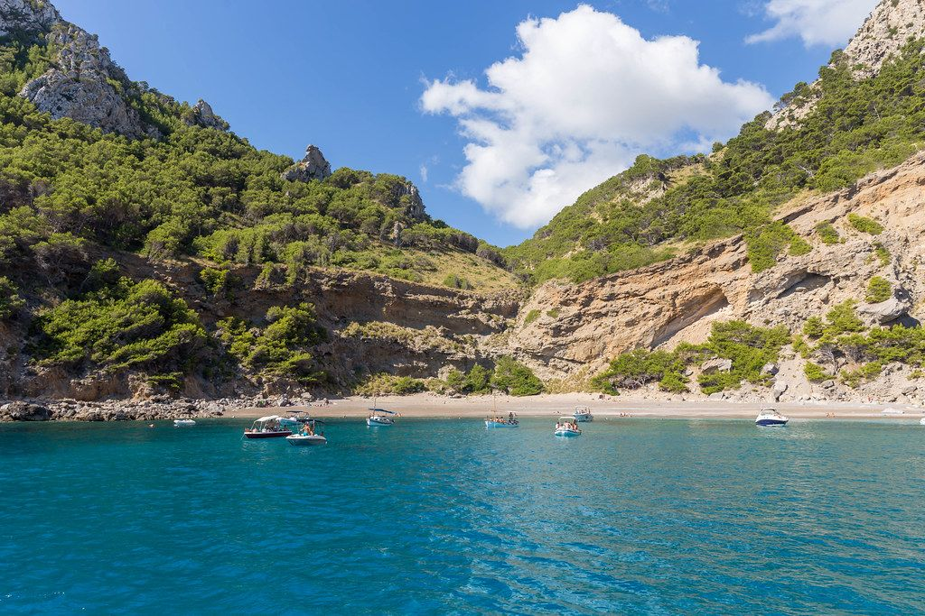 Boats in front of Platja des Coll Baix beach near Punta des Gavinot on Mallorca. View from the sea