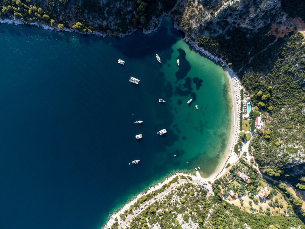 Boats in the emerald green waters of the bay of Limnonari, Skopelos. Drone photo, top view
