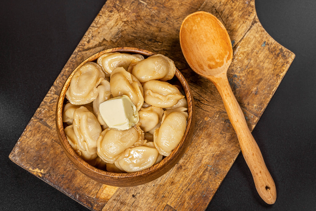 Boiled dumplings with butter on a dark background with a wooden spoon, top view