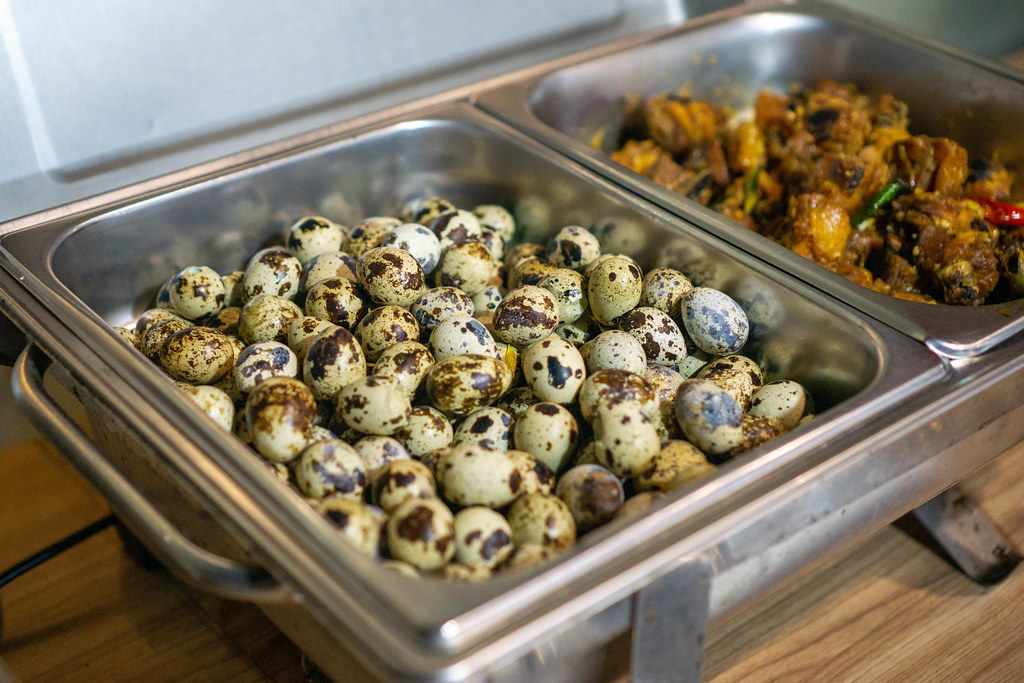 Boiled Quail Eggs and Chicken fried in Fish Sauce in a Catering Food Warmer at a Buffet in a Restaurant