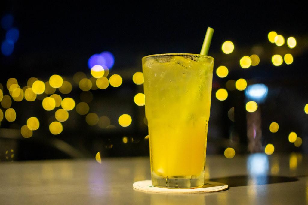 Bokeh Foto von einem Maracuja Mocktail mit Eiswürfel und Zitronengras Strohhalm in einem Cocktail Glas mit Lichtern im Hintergrund in einer Rooftop Bar