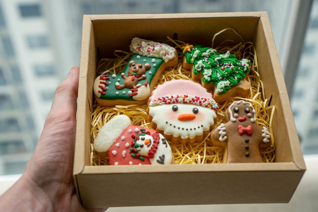 Bokeh Photo of Person holding a Paper Gift Box with Christmas Gingerbread Cookies in Different Christmas Theme Designs