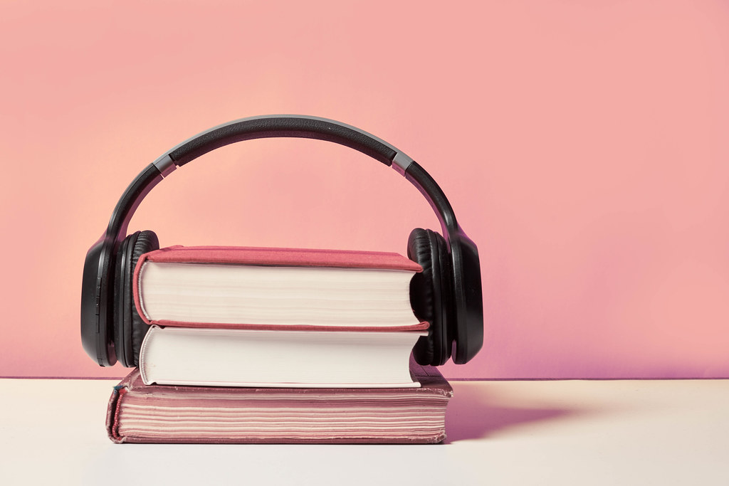 Books and modern headphones on light pink background, space for text