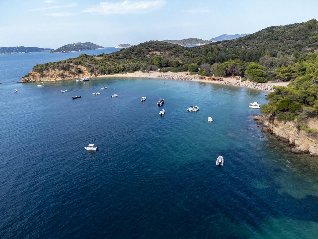 Boote erreichen den Sandstrand Tsoungrias auf der kleinen Insel bei Skiathos. Luftbild