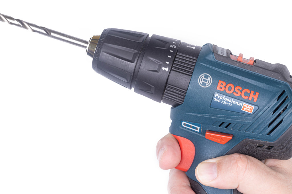 Bosch Drill in the hand with large drill above white background