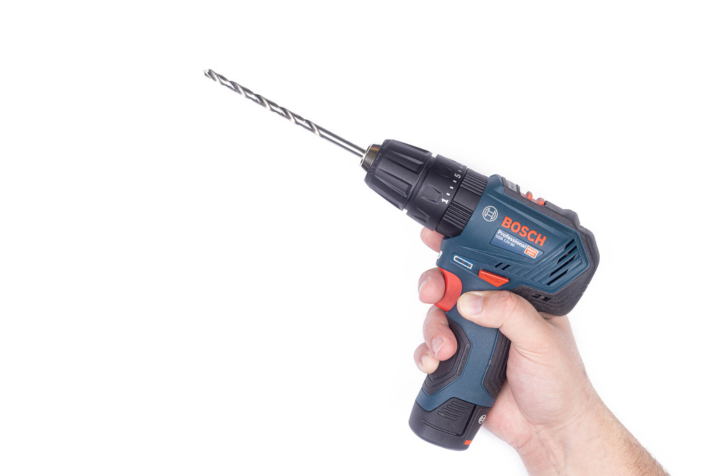 Bosch Drill in the hand with large drill with copy space