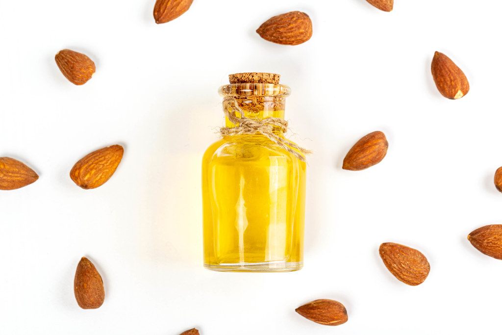 Bottle of almond oil and almonds on white background, top view